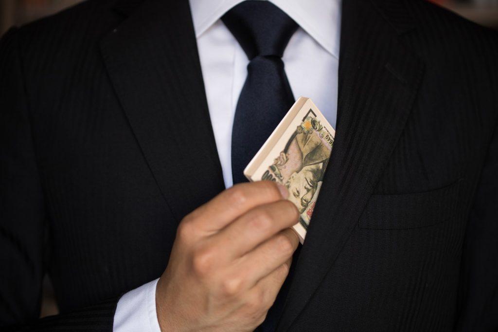 スーツを着た男がお金を懐に