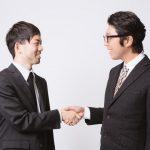 男性2人が握手する姿